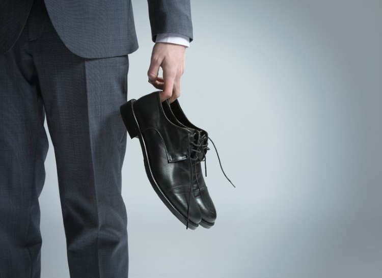 Professional Holding a Pair of Black Dress Shoes